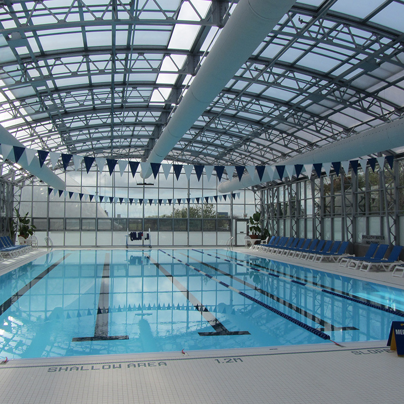 Indoor community pool construction with glass roof.